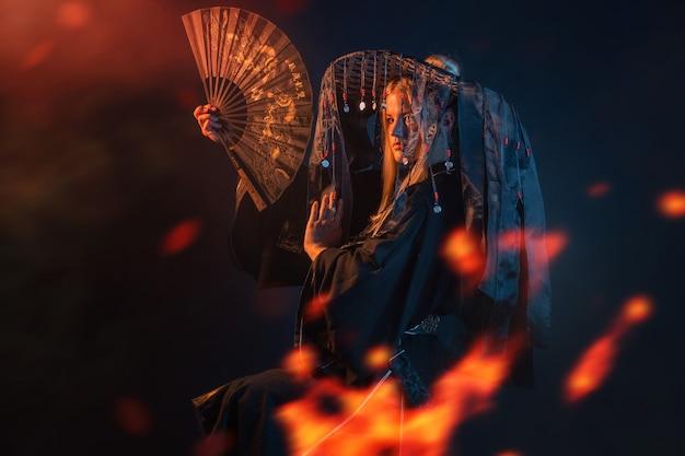 Postać w stylu azjatyckim w kimonie i słomkowym kapeluszu ze wstążkami wśród ognia