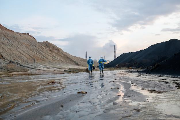 Postacie dwóch naukowców w niebieskich kombinezonach ochronnych poruszających się drogą pokrytą błotem otoczoną wzgórzami i rurami przemysłowymi