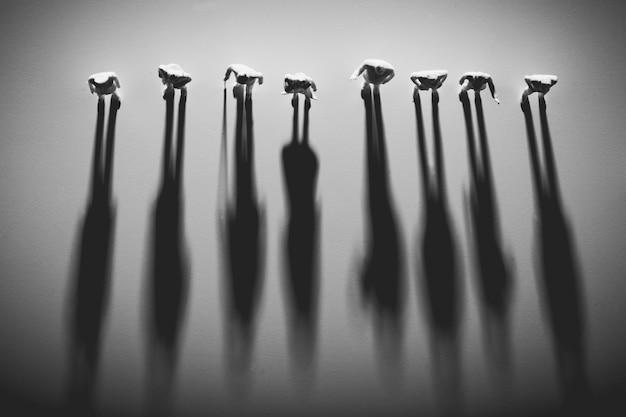 Postacie ludzi stojących w rzędzie, rzucające cień.