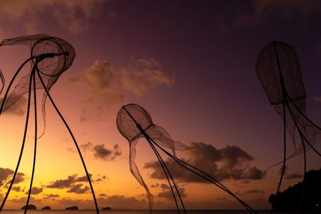 Postacie meduz na tle kolorowy zachód słońca.