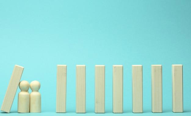 Postacie mężczyzn powstrzymują spadające z drewnianych klocków efekt domina na niebieską powierzchnię. koncepcja pracy zespołowej