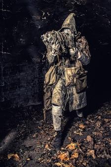 Postapokaliptyczny ocalały, tajemniczy podziemny stwór, stalker w masce gazowej i szmatach z runami, uzbrojony w ręcznie robiony pistolet, ukrywający się w lochach, opuszczonym tunelu lub miejskich ciemnych katakumbach, w odcieniach sepii