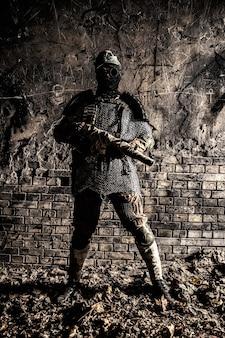 Postapokaliptyczny ocalały, żołnierz iii wojny światowej, partyzant globalnego konfliktu nuklearnego lub stalker, w wojskowej czapce i ręcznie robionej zbroi kuloodpornej, strzelającej z pistoletu maszynowego zawiniętego w opuszczony bunkier lub kopalnię