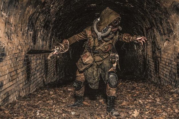 Postapokaliptyczny zmutowany stwór lub ocalały w strzępach i masce gazowej wyskakuje z ciemności i atakuje ręcznie robioną maczetą w opuszczonym tunelu, przerażającym lochu lub starym miejskim kolektorze ścieków