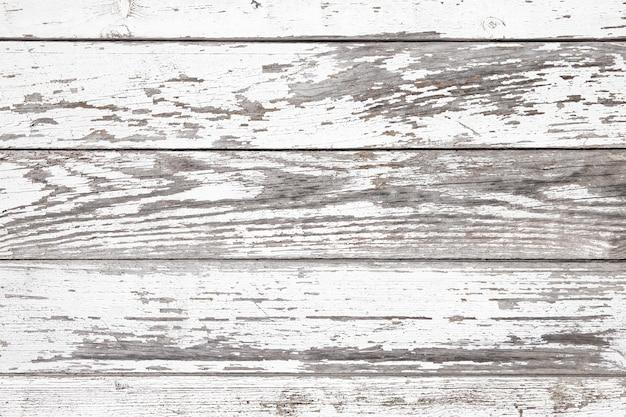 Postarzane białe drewniane panele z popękaną i łuszczącą się farbą