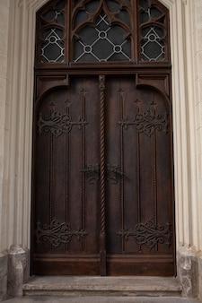 Postarzane lakierowane drzwi z ręcznie robioną klamką i metalowym kuciem