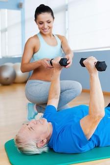 Postęp z dnia na dzień. pewna siebie fizjoterapeutka wspierająca starszego mężczyznę w ćwiczeniach siłowych