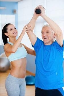 Postęp z dnia na dzień. wesoła fizjoterapeutka pomaga starszemu mężczyźnie w fitness w klubie fitness