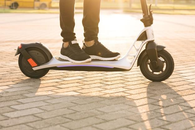 Postrzelony na nogach młody hipster mężczyzna w czarnych trampkach jeździ na elektrycznym skuterze o zachodzie słońca
