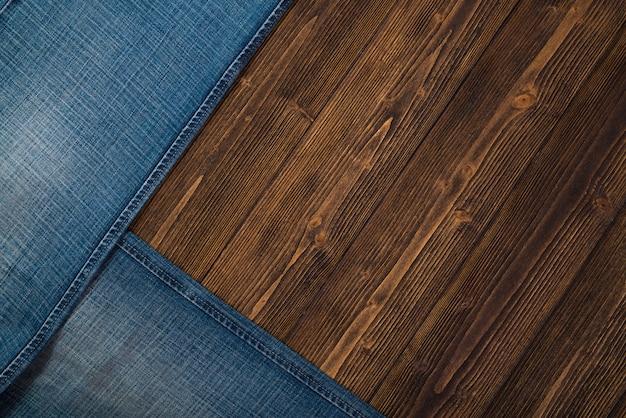 Postrzępione dżinsy lub dżinsowa kolekcja dżinsów na drewnie