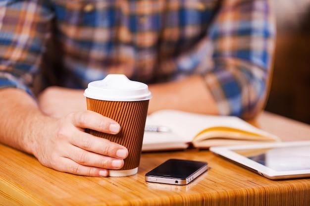 Poświęć czas na przerwę na kawę. zbliżenie: mężczyzna trzymający filiżankę kawy siedząc przy biurku z notatnikiem i cyfrowym tabletem leżącym na nim