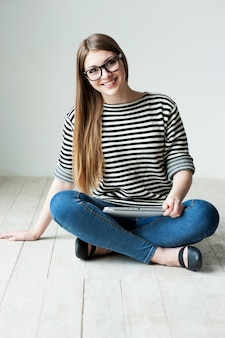 Poświęć czas na relaks. piękna młoda kobieta w pasiastym ubraniu siedzi na podłodze i uśmiecha się