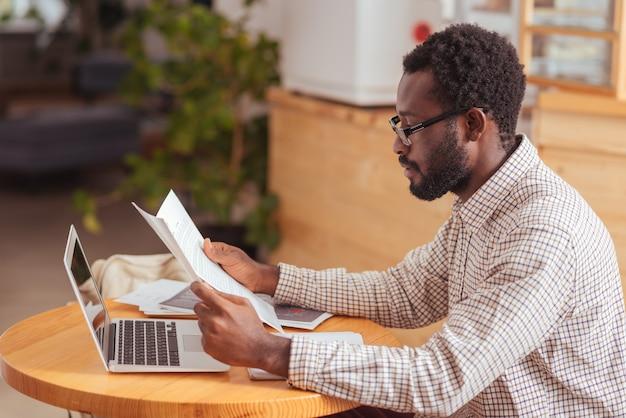 Poświęcanie dużo uwagi. przystojny młody mężczyzna siedzi w kawiarni i uważnie czyta raport, zwracając uwagę na każdy szczegół
