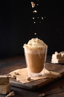 Posyp halawą w modnej recepturze kawy latte z chałwą w nowoczesnej szklanej filiżance na ciemnym tle