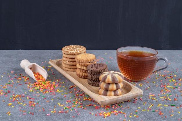 Posyp rozsypane cukierki, miarka, filiżanka herbaty i różne ciasteczka