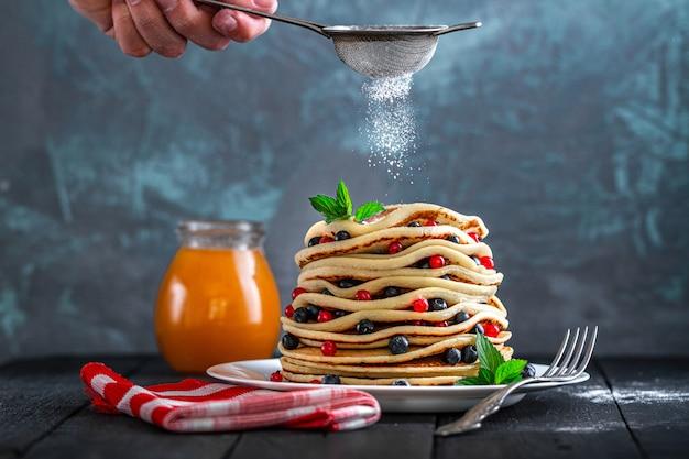 Posyp sproszkowane cukierkowe domowe naleśniki ze świeżymi jagodami i miętą na pyszne słodkie śniadanie
