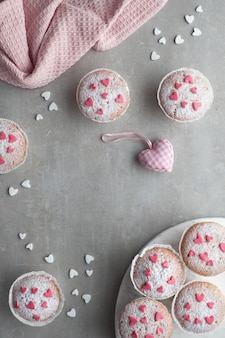 Posypane cukrem babeczki z różowymi i białymi serduszkami z kremówki