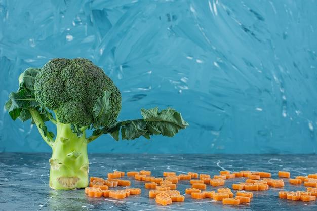 Posypany makaronem i świeżymi brokułami na marmurowej powierzchni