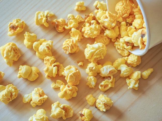 Posypany popcorn na drewnianym stole. bałagan na stole.