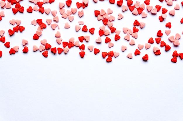 Posypuje tło, posypuje cukrem czerwone serca, dekorację na ciasto i piekarnię. widok z góry, płaski układ. święta walentynkowe.