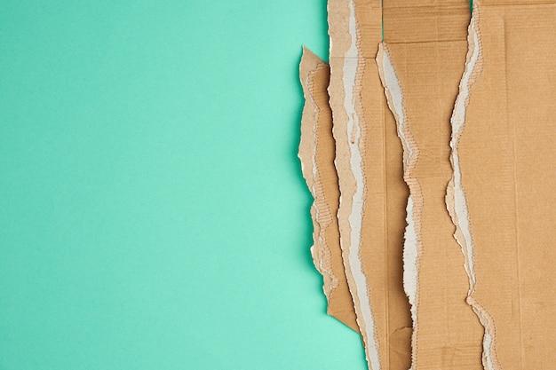 Poszarpane krawędzie tektury falistej brązowego papieru tekturowego na zielonym tle