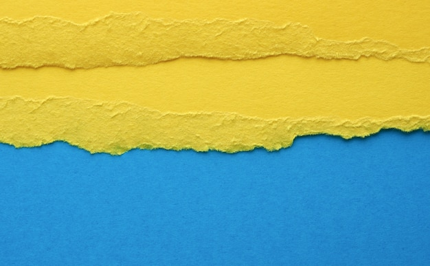 Poszarpane krawędzie żółtego papieru na niebieskim tle