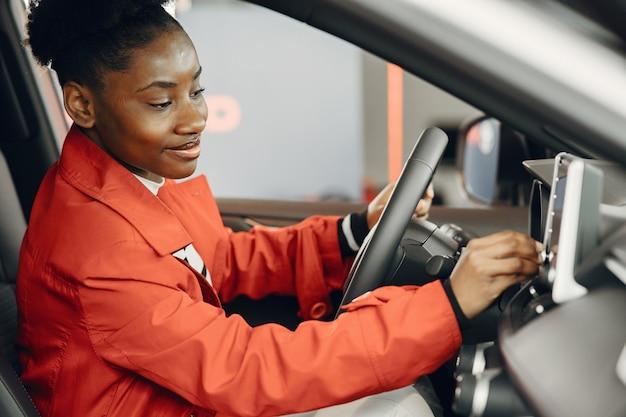 Poszedłem dziś na zakupy. ujęcie atrakcyjnej afrykańskiej kobiety siedzącej w salonie samochodowym.