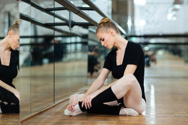 Poszkodowana baletnica w pointach siedząca na podłodze w klasie baletowej
