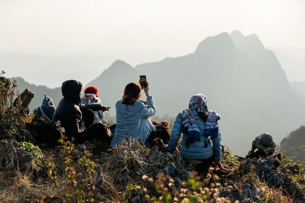 Poszukiwacz przygód i turyści ubrani w ocieplany płaszcz, kurtkę i szalik, robią zdjęcia gór