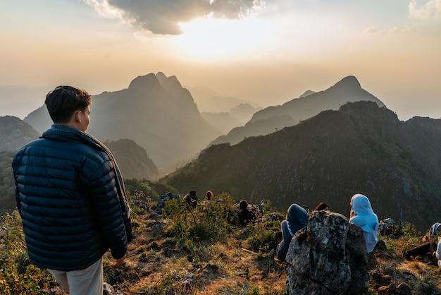 Poszukiwacz przygód ubrany w niebieski ocieplany płaszcz z turystami w górach