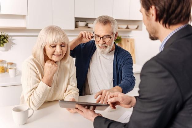 Poszukiwanie Przyszłego Zakupu. Ciekawa Sympatyczna, Zachwycona Starsza Para Spotyka Się Z Agentem Nieruchomości I Konsultuje Się Z Nim Przy Użyciu Nowoczesnego Urządzenia Premium Zdjęcia