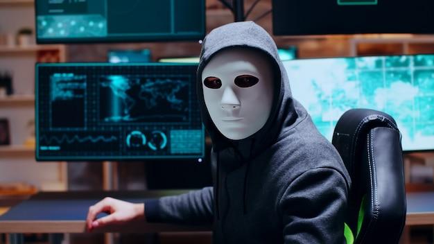 Poszukiwany cyberprzestępca w białej masce i patrzący w kamerę.