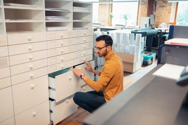 Poszukuje materiałów. widok z góry ciemnowłosego mężczyzny w okularach szukającego materiałów w drukarni