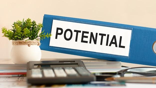 Potencjał - niebieski segregator na biurku w biurze z kalkulatorem, długopisem i zieloną rośliną doniczkową. może być stosowany do koncepcji biznesowych, finansowych, edukacyjnych, audytu i podatków. selektywna ostrość.