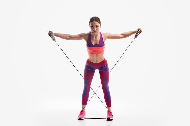 Potężna kobieta ćwicząca z liną oporową