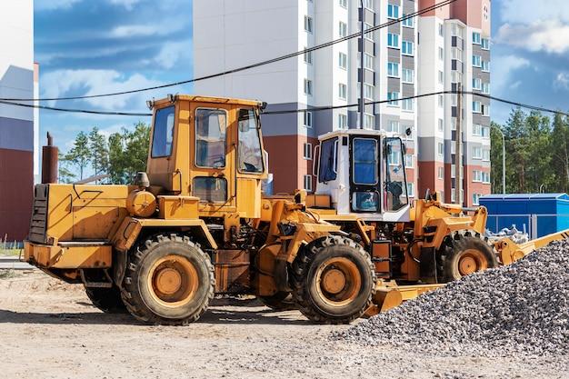 Potężna ładowarka kołowa do transportu towarów wielkogabarytowych na budowie nowoczesnej dzielnicy mieszkalnej. sprzęt budowlany do podnoszenia i przenoszenia ładunków.