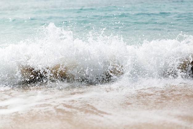 Potężna niebieska fala pęka wzdłuż brzegu.
