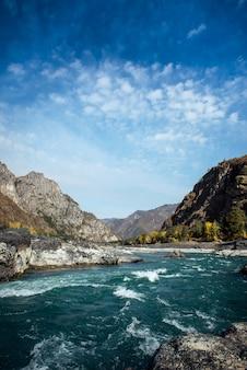 Potężna rzeka płynie kamienistymi brzegami wśród skalistych gór na tle czystego, błękitnego nieba. turkusowa woda burzowej rzeki i ogromnych kamieni.