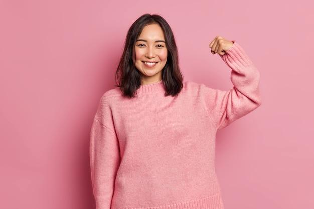 Potężna, wesoła brunetka podnosi rękę i pokazuje mięśnie, demonstrując swoją siłę, wygląda pewnie na oczach kamery, uśmiecha się delikatnie, nosi swobodny sweter z długimi rękawami