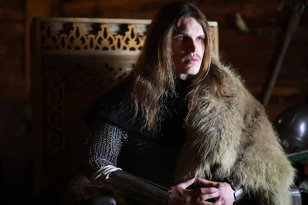 Potężny bohater z długimi włosami w zbroi kolczugowej w starożytnej sali. średniowieczny wojownik w komnatach rycerza.