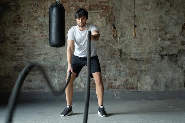 Potężny człowiek trenujący z liną w treningu funkcjonalnym fitness gym crossfit liny ćwiczenia podczas treningu sportowca na siłowni treningu
