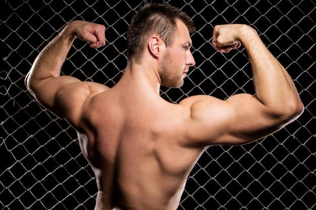 Potężny facet pokazuje jego mięśnie na ogrodzeniu