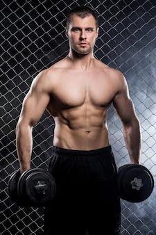 Potężny facet z dumbbells pokazuje mięśnie na ogrodzeniu