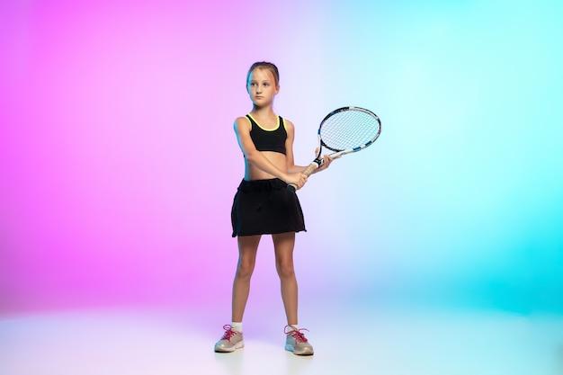 Potężny. mała tenisistka w czarnej odzieży sportowej odizolowana na ścianie gradientowej
