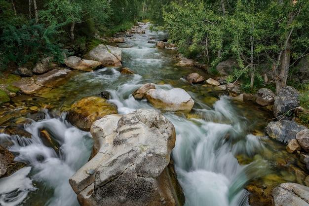 Potężny nurt górskiej rzeki, ogromne głazy, brzegi porośnięte zielenią