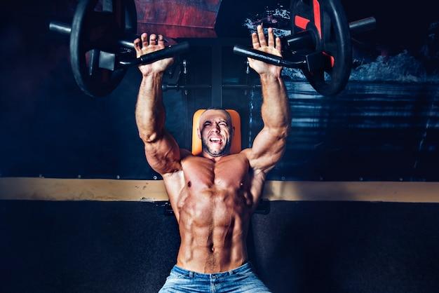 Potężny sportowiec wykonujący ćwiczenia na mięśnie piersiowe