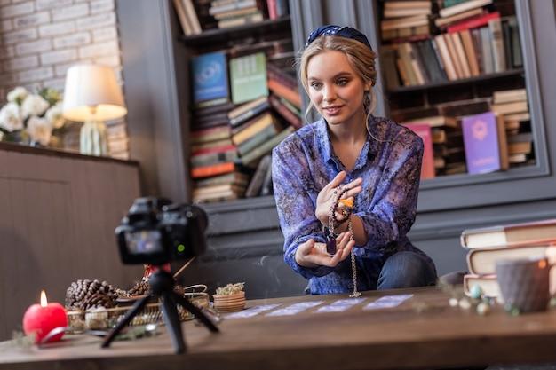Potężny talizman. zachwycona miła kobieta pokazująca amulet siedząc przed kamerą