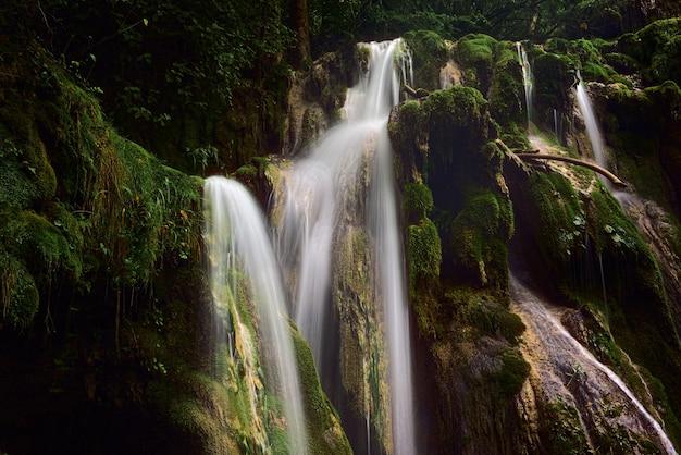 Potężny wodospad w lesie w pobliżu omszałych formacji skalnych