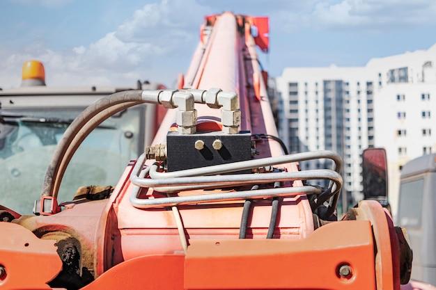 Potężny wózek widłowy kołowy z masztem teleskopowym na budowie nowoczesnego osiedla. sprzęt budowlany do podnoszenia i przenoszenia ładunków.