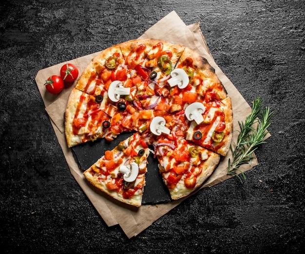 Potnij meksykańską pizzę na papierze na czarnym rustykalnym stole.